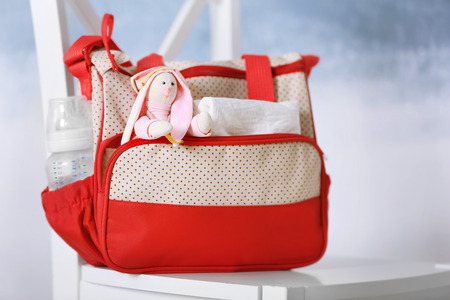 Mothers bag with toy and accessories on chair Foto de archivo