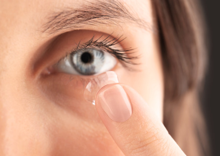 Close up view of young woman putting contact lens in her eye Foto de archivo