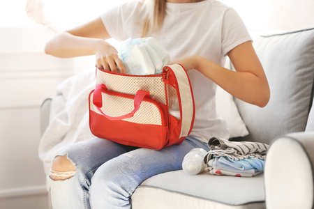 Woman packing her bag with child stuff on couch Stockfoto