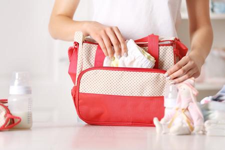 Donna che prepara la sua borsa con roba per bambini