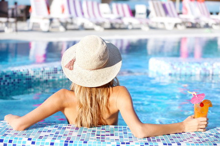 Beautiful young woman with cocktail in swimming pool