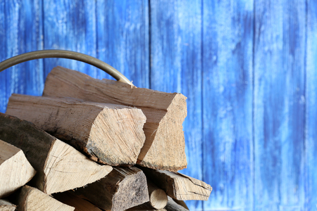 Stack of firewood on blue wooden background