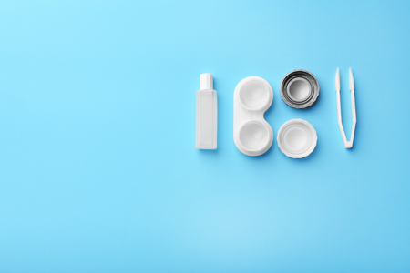 Container with contact lenses, tweezers and bottle of solution on blue background, close up view Stock Photo