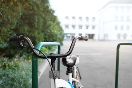Close up view of bicycle parked outdoors, on blurred background