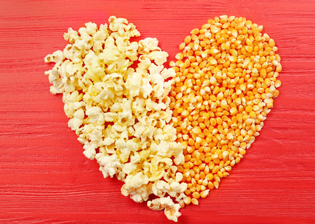 Heart made of popcorn and maize grains on red wooden background, top view