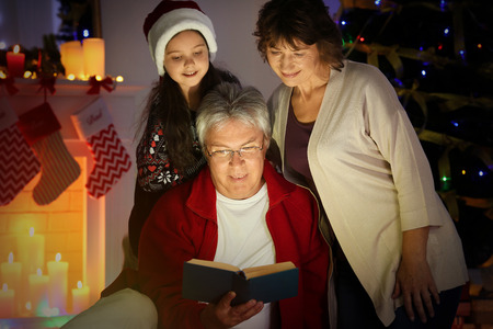 Little girl and her grandparents reading book in living room decorated for Christmas 스톡 콘텐츠 - 109426096
