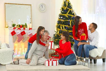 Happy family in living room giving Christmas presents to each other