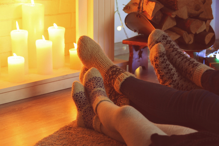 Legs in socks near fireplace, close up view