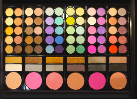 Assortment of different colourful eye shadow palettes in cosmetic store