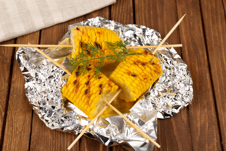 Grilled corns with ingredients on foil