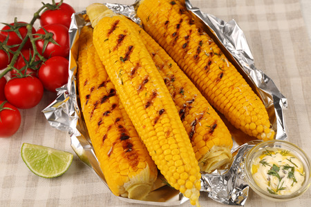 Grilled corns with cherry tomatoes and ingredients on table 写真素材 - 107789105