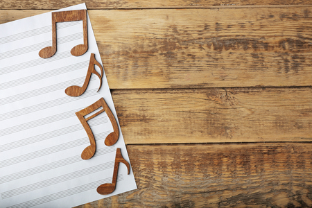 Music notes and sheet of paper on wooden background