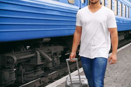 Young man in blank t-shirt walking along railway platform with suitcase, closeup Stock fotó