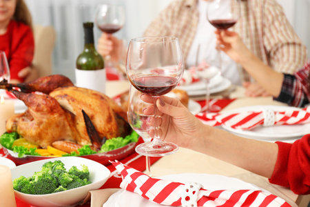 People sitting at table served for Thanksgiving dinner, close up view Stock Photo