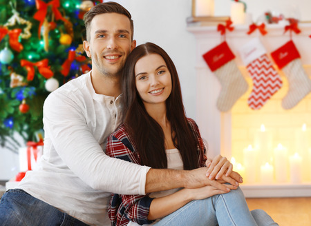 Beautiful young couple in living room decorated for Christmas