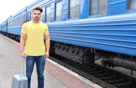 Young man in blank t-shirt standing on railway platform with suitcase