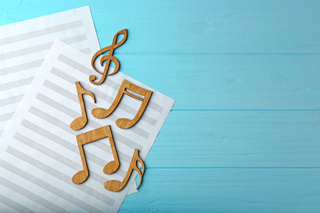 Music notes and sheets of paper on color wooden background Standard-Bild
