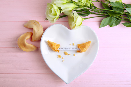 Plate with fortune cookie on wooden background