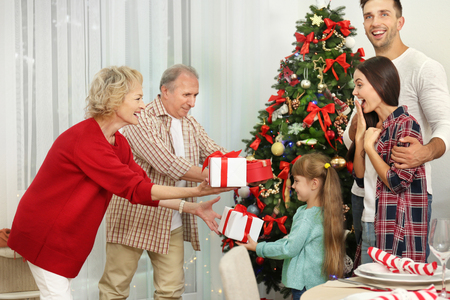 Happy members of family giving Christmas presents to each other Stock Photo