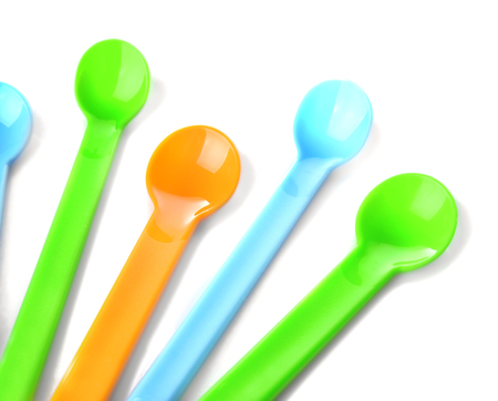 Colorful plastic spoons for child on white background