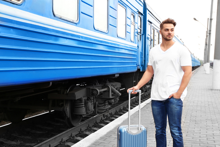 Young man in blank t-shirt with suitcase standing on railway platform near train Stock fotó