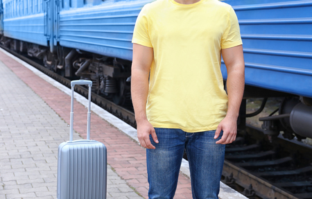 Young man in blank t-shirt standing on railway platform with suitcase, closeup Stock fotó