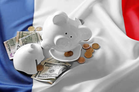 Broken piggy bank on flag background