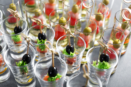 Fresh tasty canapes in glass cups, closeup
