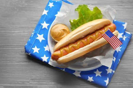 Tasty hot dog with American flag on table