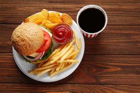 Tasty burger with snacks and coke on wooden table Stok Fotoğraf
