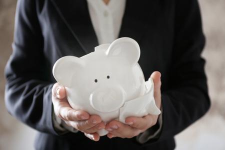 Woman holding broken piggy bank Stok Fotoğraf