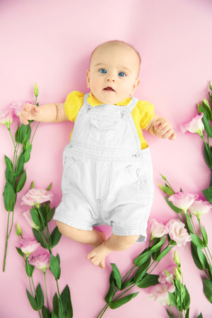 Cute baby and eustoma flowers on pink background