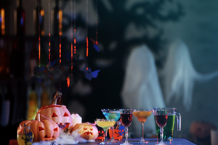 Different colorful cocktails and decor prepared for Halloween party, on blurred background