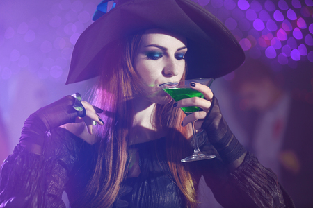 Young woman in witch costume drinking cocktail at Halloween party, close up