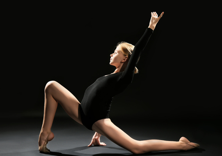 Young girl doing gymnastic exercise on dark background