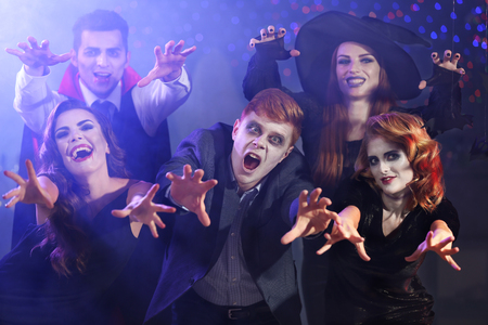 Young people in costumes having fun at Halloween party Stock Photo