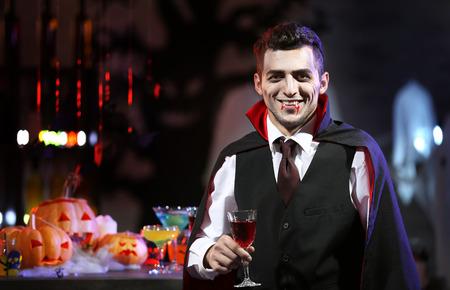 Jeune homme habillé en cocktail de vampire à la fête d'Halloween