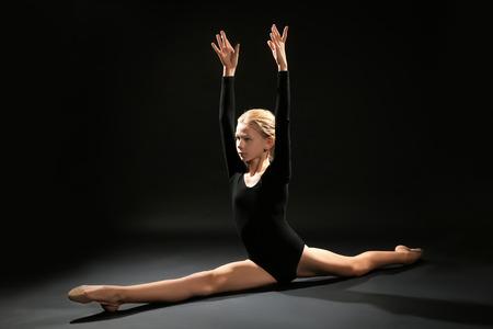 Junges Mädchen, das Gymnastikübung auf dunklem Hintergrund tut