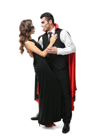 Jeune couple habillé en costumes de vampire pour Halloween, isolé sur blanc