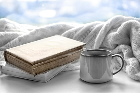 Hot drink with books and plaid on windowsill Stock Photo
