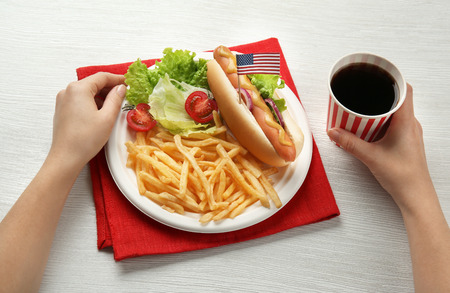 Woman with hot dog, french fries and cola on wooden background