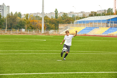 Boy playing football at stadium Stock Photo
