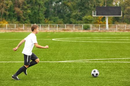 Boy playing football at stadium 免版税图像