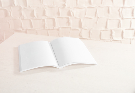 blank brochure on white wooden table against textured wall stock