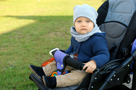 Cute little baby sitting in stroller outdoors