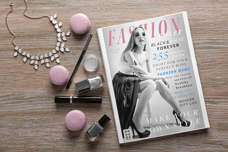Makeup products, magazine and macaroons on wooden background