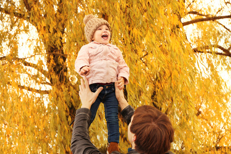 Father holding cute little girl while standing under tree in park