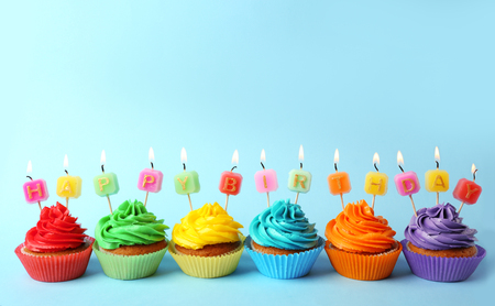Tasty colorful cupcakes with Happy Birthday candles on blue background