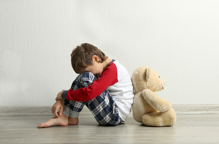 Sad little boy with teddy bear sitting on floor in empty room Stockfoto