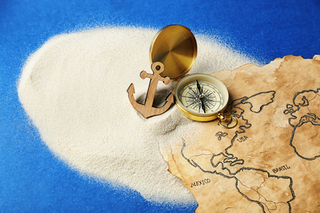 Compass, anchor and old map in sand on blue background. Columbus Day concept Banque d'images